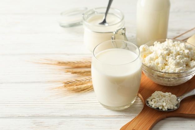 Espiguillas de trigo, productos lácteos y tablero sobre fondo de madera blanca