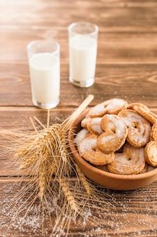 Espiguillas de trigo sobre la mesa y galletas con azúcar y leche en bokallah de vidrio