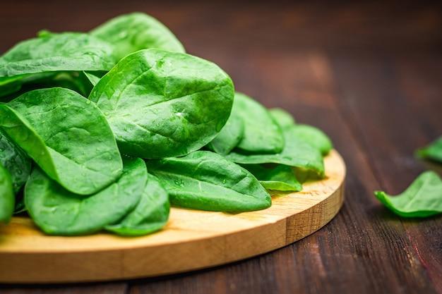 La espinaca jugosa fresca se va en una tabla marrón de madera. productos naturales, verdes, alimentos saludables.