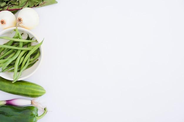 Espinacas; cebolla; judías verdes; pepino; pimiento y cebolleta aislados sobre fondo blanco