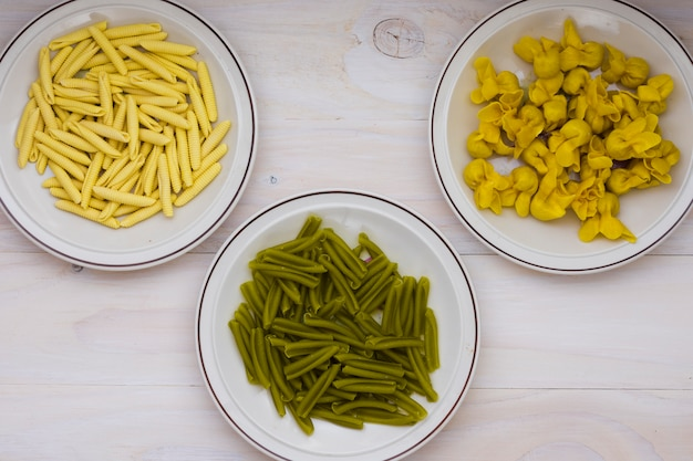 Espinacas italianas secas casarecce; pasta de garganelli y tortellini sobre fondo de madera