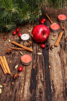 Espíritu árbol de navidad, manzana fresca, canela, velas, cardamomo, anís estrellado. decoraciones de la naturaleza, tableros de madera vintage