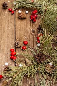 Espíritu navidad en mesa de madera. bayas frescas de rosa de perro, caramelos de bolas, ramas y conos de pino, nieve artificial. decoraciones de la naturaleza, tableros de madera vintage
