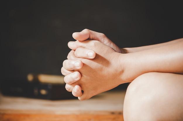 Espiritualidad y religión, las manos juntas en oración en una santa biblia en el concepto de iglesia para la fe.