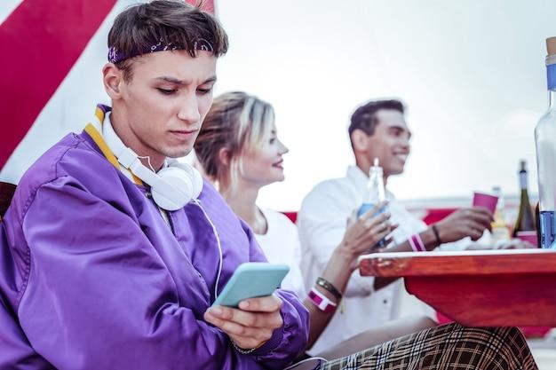 Espíritus bajos. estudiante encantado negativo cruzando los brazos sobre el pecho mientras mira su dispositivo