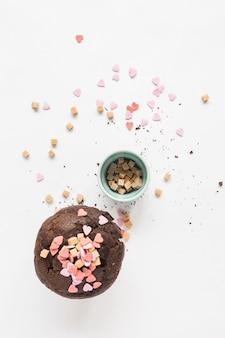 Espolvorea en chocolate marrón de la magdalena sobre el fondo blanco