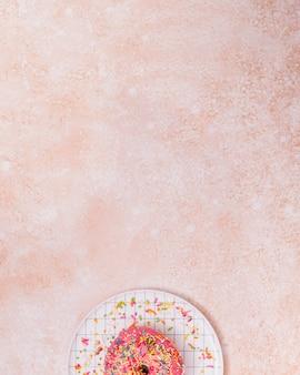 Espolvoree sobre la rosquilla rosada sobre el plato a cuadros con un fondo rústico con copyspace para escribir el texto