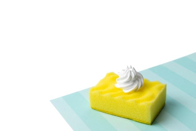Esponja amarilla para lavavajillas con espuma sobre fondo azul y blanco. concepto de servicio de limpieza