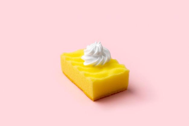 Esponja amarilla para lavavajillas con espuma sobre fondo rosa. concepto de servicio de limpieza