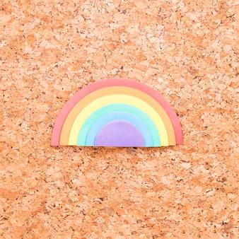 Esponja arco iris colocada en el centro de fondo de tablero de corcho