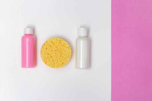 Esponja facial de color amarillo, crema hidratante, limpiador en pequeñas botellas sobre papel.