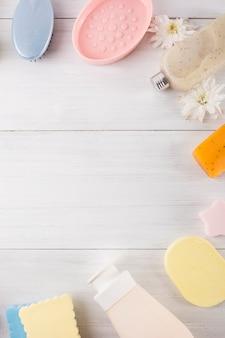 Esponja; flor; fregar; jabón y pincel sobre fondo con textura de madera