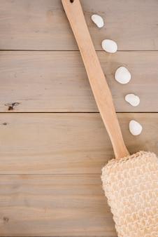Esponja vegetal con mango largo de madera y guijarros