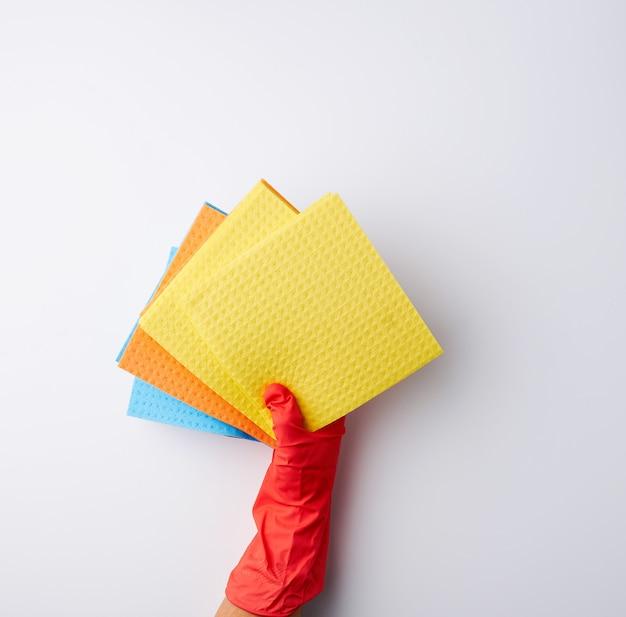 Esponjas absorbentes cuadradas multicolores en sus manos con guantes de goma roja