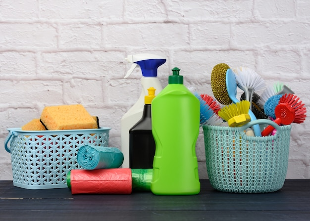 Esponjas, cepillos de plástico y botellas de detergentes en una mesa de madera azul