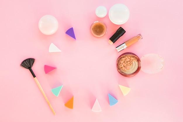 Esponjas cosméticas de diferentes colores con productos de maquillaje sobre fondo rosa.