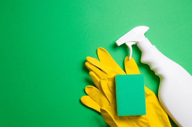 Esponjas guantes de goma y una botella de spray blanco para detergente sobre un fondo verde