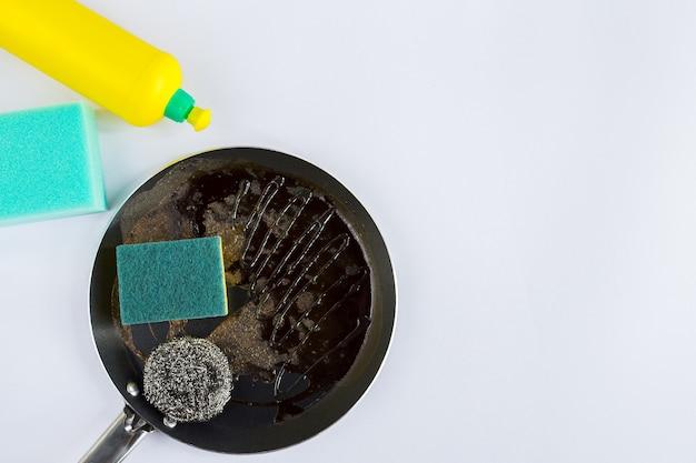 Esponjas y lana de acero para limpiar una sartén con líquido para lavar platos