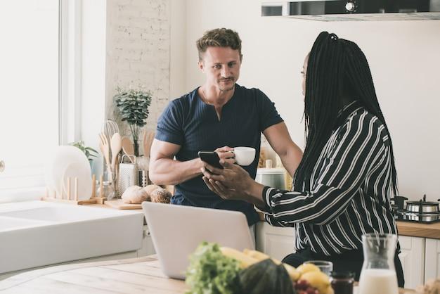 Esposa afroamericana que muestra información sobre un teléfono inteligente a su esposo durante el desayuno