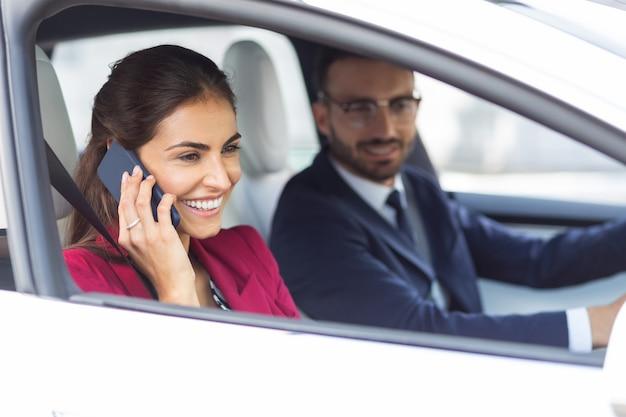 Esposa alegre. esposa morena atractiva alegre hablando por teléfono mientras el marido conduce