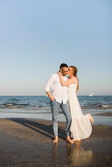 Esposa besando a su marido cerca de la orilla del mar en la playa