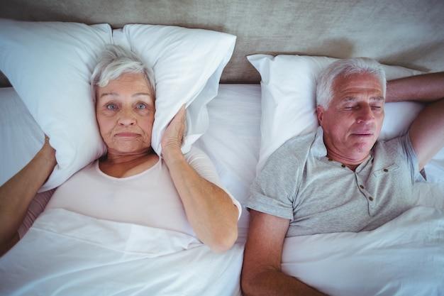 Esposa bloqueando las orejas con almohada mientras el esposo ronca en la cama