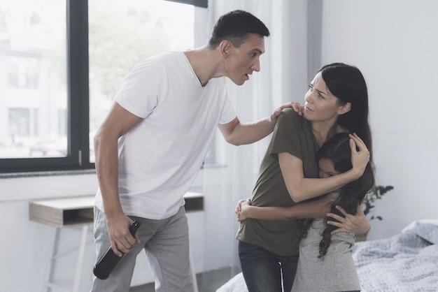 La esposa está en el dormitorio y protege, abrazando a su hija.