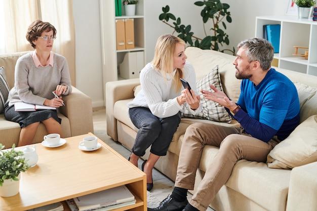 Esposa enojada mostrando sms de amante a esposo en sesión de psicología