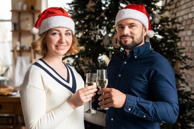 Esposa y esposo animando con copas de champán en el día de navidad