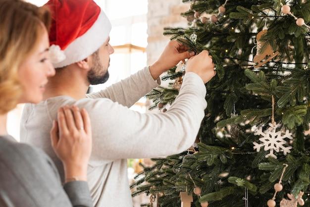 Esposa y esposo decorando el árbol con espacio de copia