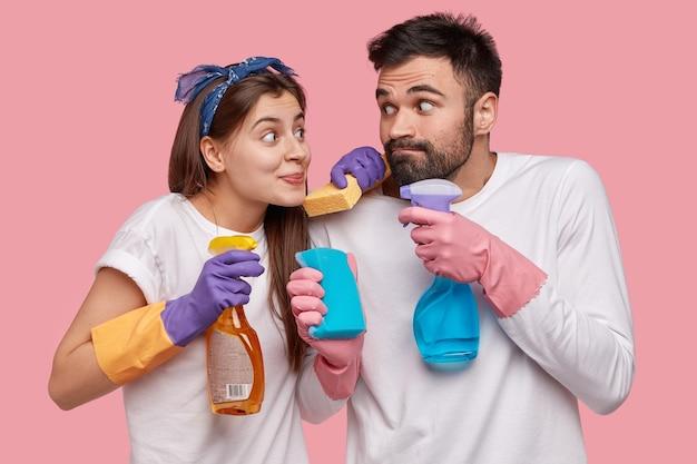 La esposa y el esposo europeos divertidos sostienen un trapeador y una botella de spray, usan guantes protectores de goma