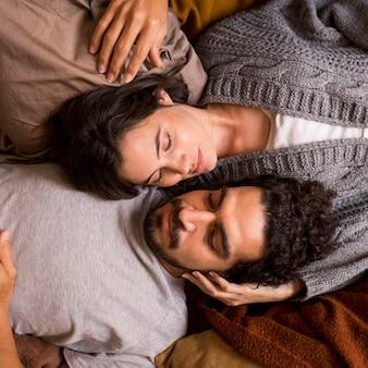 Esposa y esposo de vista superior acostados juntos en la cama