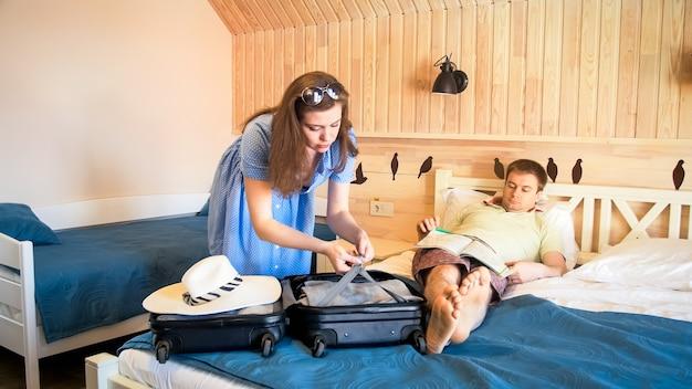 Esposa joven desembalaje de la maleta después de llegar a la habitación del hotel