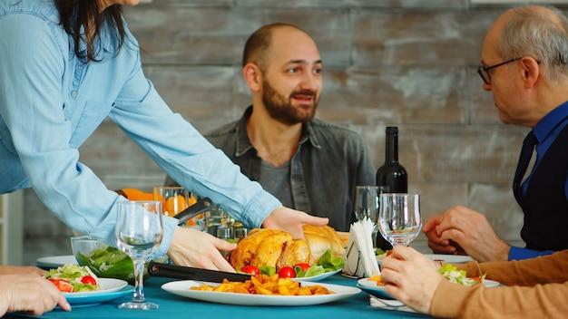 Esposa joven poniendo pollo sabroso en la mesa para su almuerzo familiar.