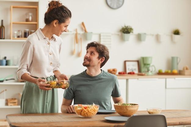 Esposa joven trayendo el plato y sirviendo la cena a su esposo, quien está sentado a la mesa en la cocina