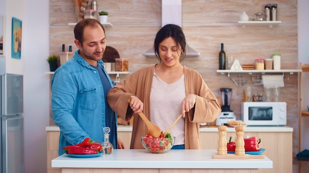 Esposa mezcla ensalada saludable en un tazón de vidrio y esposo con bolsa de papel de comestibles en la cocina. cocinar la preparación de alimentos orgánicos saludables felices juntos estilo de vida. comida alegre en familia con verduras.