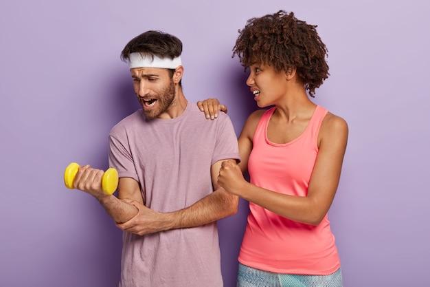 Esposa solidaria con peinado afro, mantiene la mano en el hombro del esposo, mira cómo levanta pesas pesas, trabaja en los músculos.