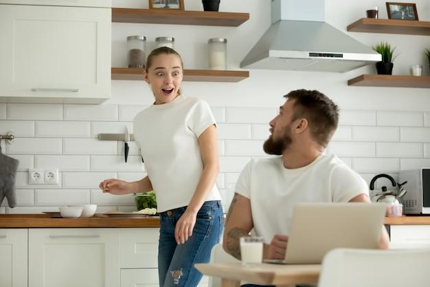 Esposa sorprendida emocionada de escuchar noticias del esposo en la cocina