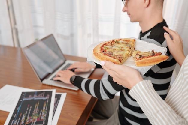 Esposa trayendo pizza al hombre trabajador