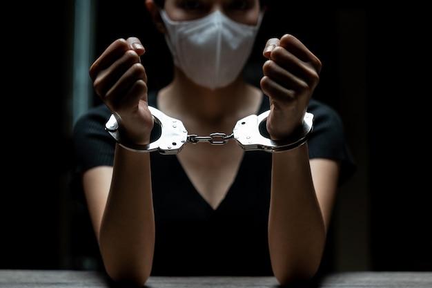 Esposadas en un prisionero, las prisioneras fueron esposadas en la oscura prisión.