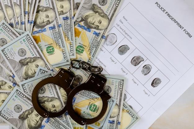 Esposas, huella digital, dólares estadounidenses en un delito de arresto, billetes de cien dólares estadounidenses