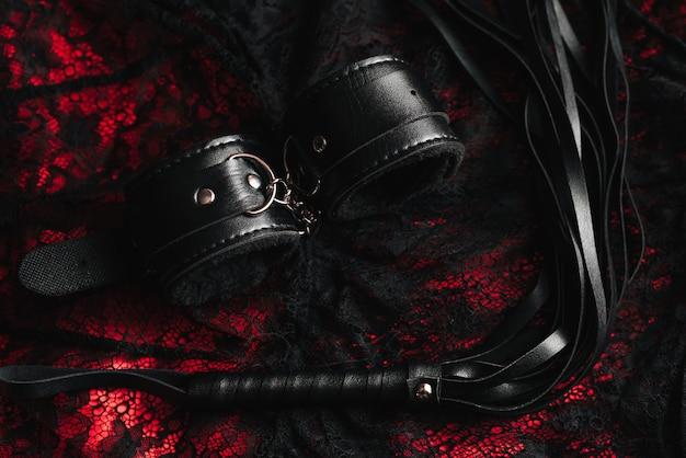 Esposas y látigo de cuero para juegos sexuales de rol bdsm
