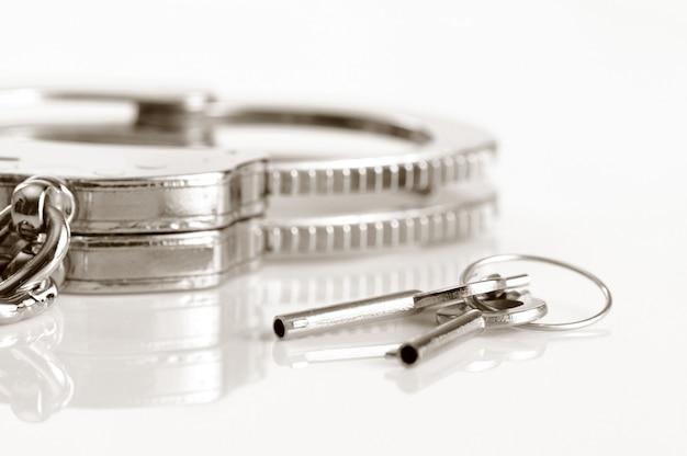 Esposas de metal y llaves aisladas sobre fondo blanco.