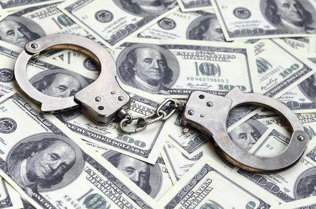 Las esposas de la policía se encuentran en un montón de billetes de un dólar