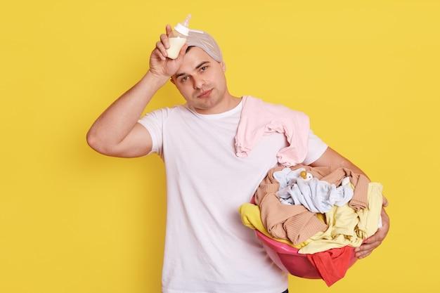 Esposo agotado cansado que se para con artículos para bebés aislados sobre una pared amarilla, el padre sostiene el biberón en las manos, mantiene la mano en la frente.
