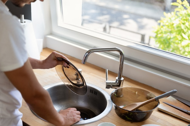 Un esposo ayuda a su esposa a hacer frente a las tareas domésticas. igualdad en las relaciones.