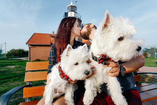 El esposo besa a su esposa, en sus brazos tienen dos lindos cachorros blancos.