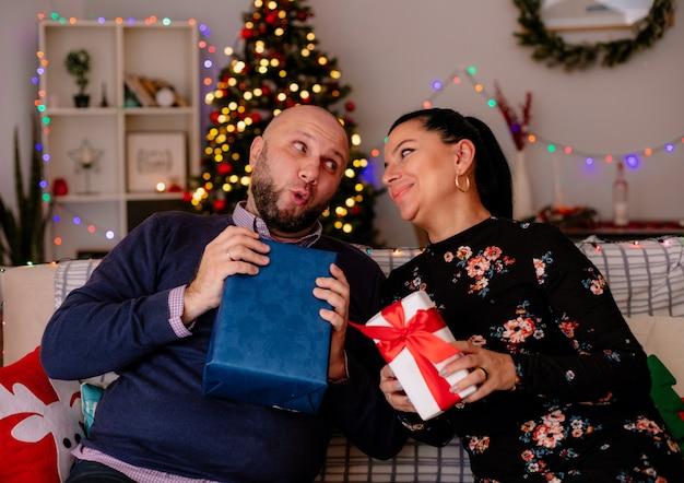 Esposo curioso y esposa complacida en casa en la época navideña sentados en el sofá en la sala de estar, ambos sosteniendo un paquete de regalo mirando el uno al otro