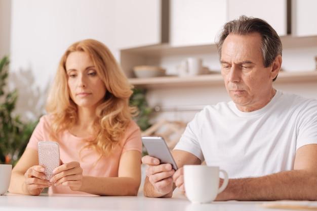 Esposo y esposa egoístas e ignorantes hábiles sentados en casa y usando dispositivos digitales sin prestar atención el uno al otro