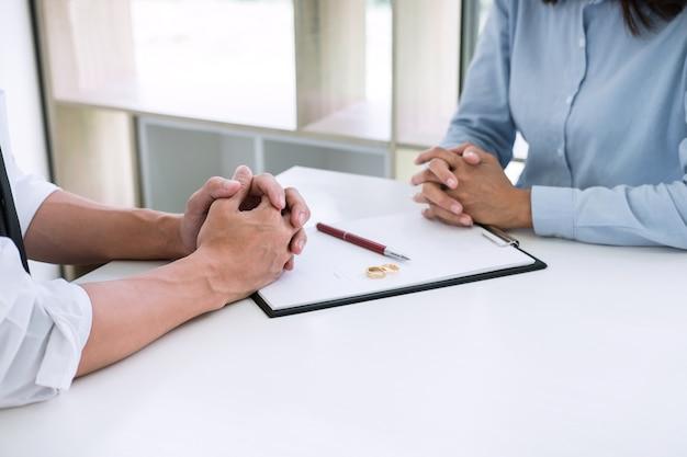El esposo y la esposa están leyendo un acuerdo de divorcio y firman un decreto de divorcio